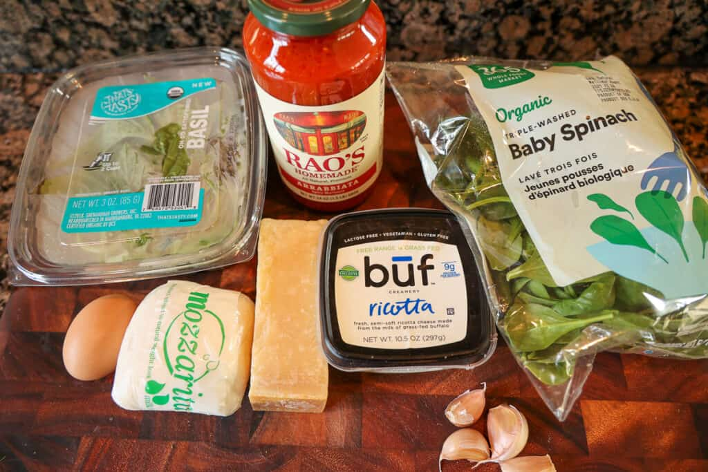 stuffed shell filling ingredients on a cutting board: cheese, spinach, basil, red sauce
