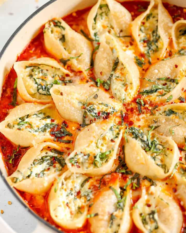 stuffed pasta shells in a baking dish with fresh basil