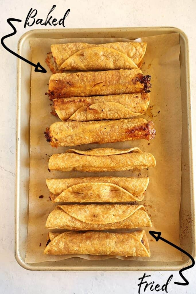 baked and fried taquitos on a baking sheet