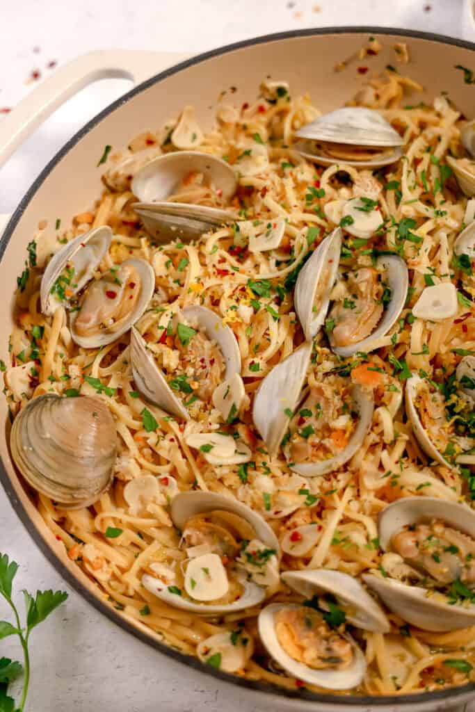 linguine and clams in a white wine sauce with breadcrumbs and fresh herbs on top