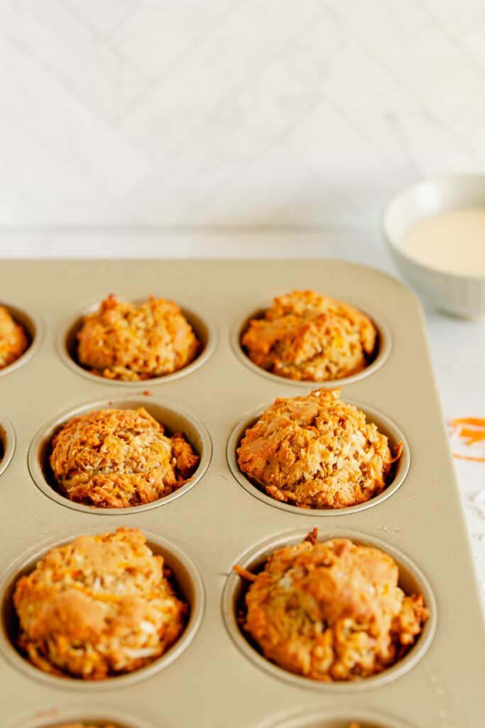 carrot cake muffins in a gold muffin tin