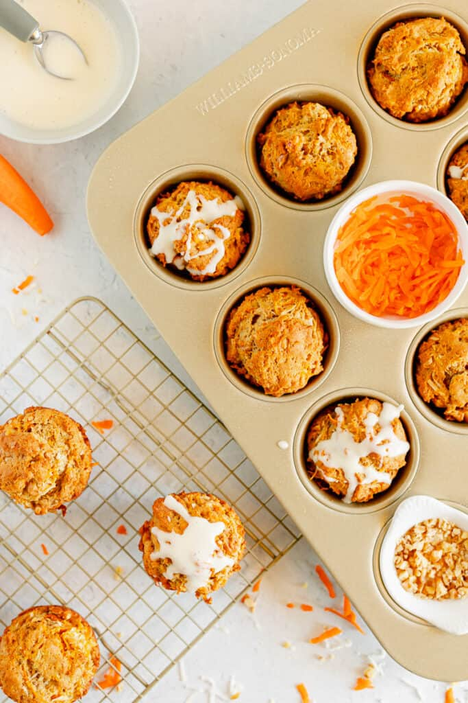muffin tin with shredded carrots, carrot cake muffins, and cream cheese glaze on top