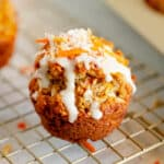 carrot cake muffin with glaze dripping off side on a gold stand