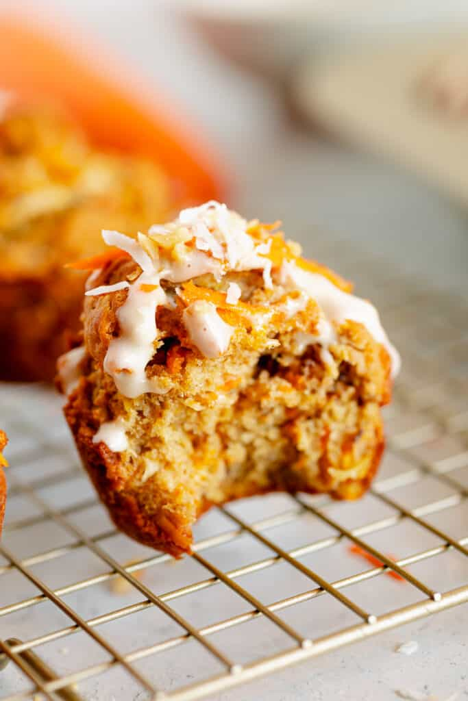 bite out of carrot cake muffin topped with cream cheese frosting