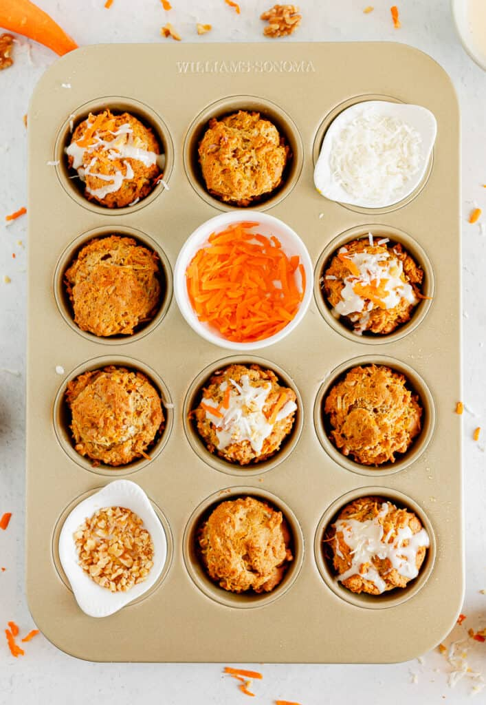 carrot cake muffins in a muffin tin with shredded carrots, coconut and walnuts