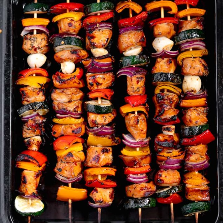 grilled chicken skewers and vegetables on a black dish