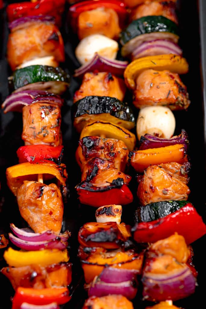 close up of grilled chicken and vegetables on a skewer