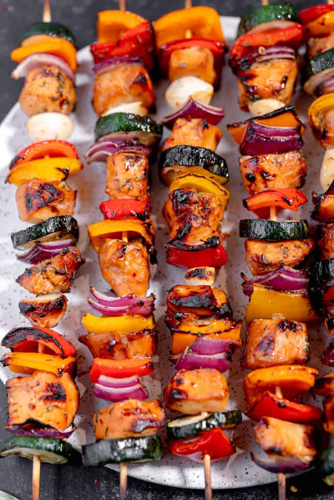 close up of grilled chicken, bell peppers, onion, and garlic on a skewer