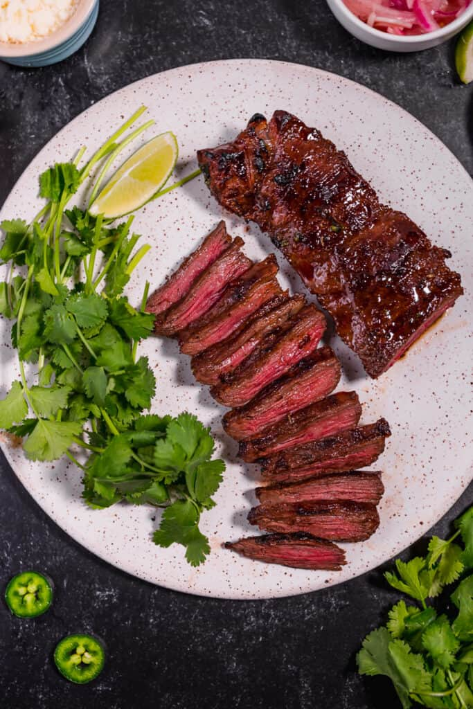 grilled carne asada skirt steak on a white plate with cilantro on a white plate