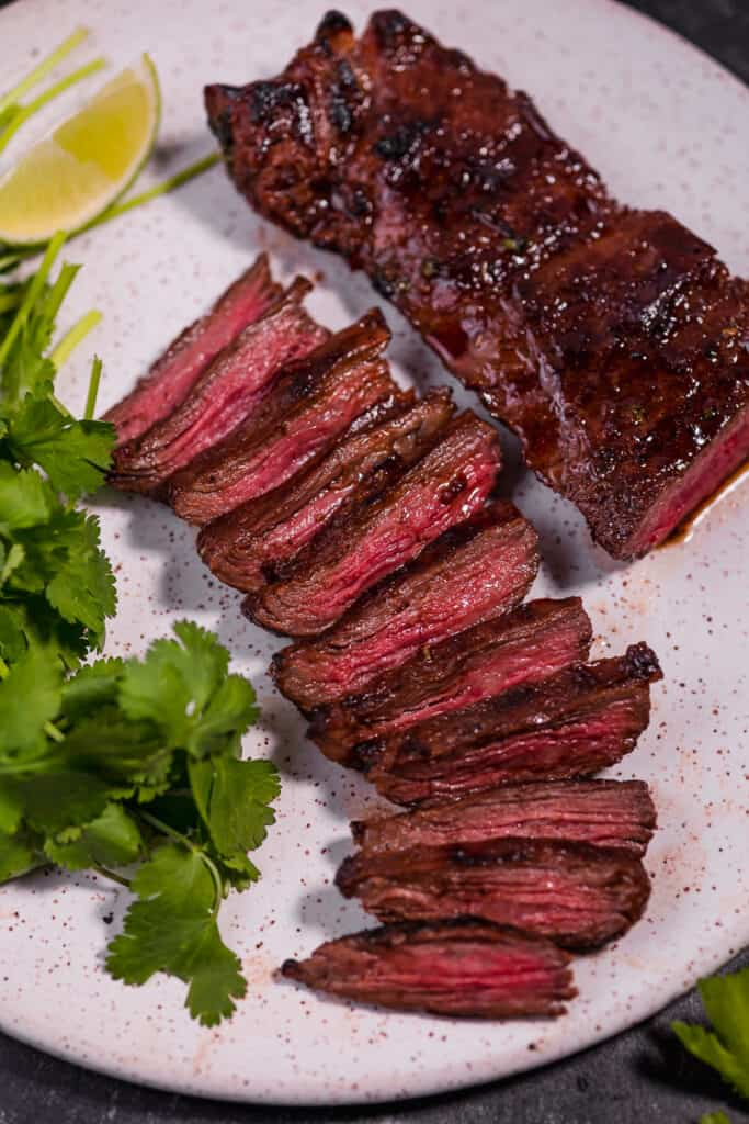 sliced carne asada skirt steak on a white plate surrounded by cilantro
