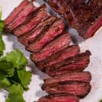 close up of sliced carne asada steak on white plate