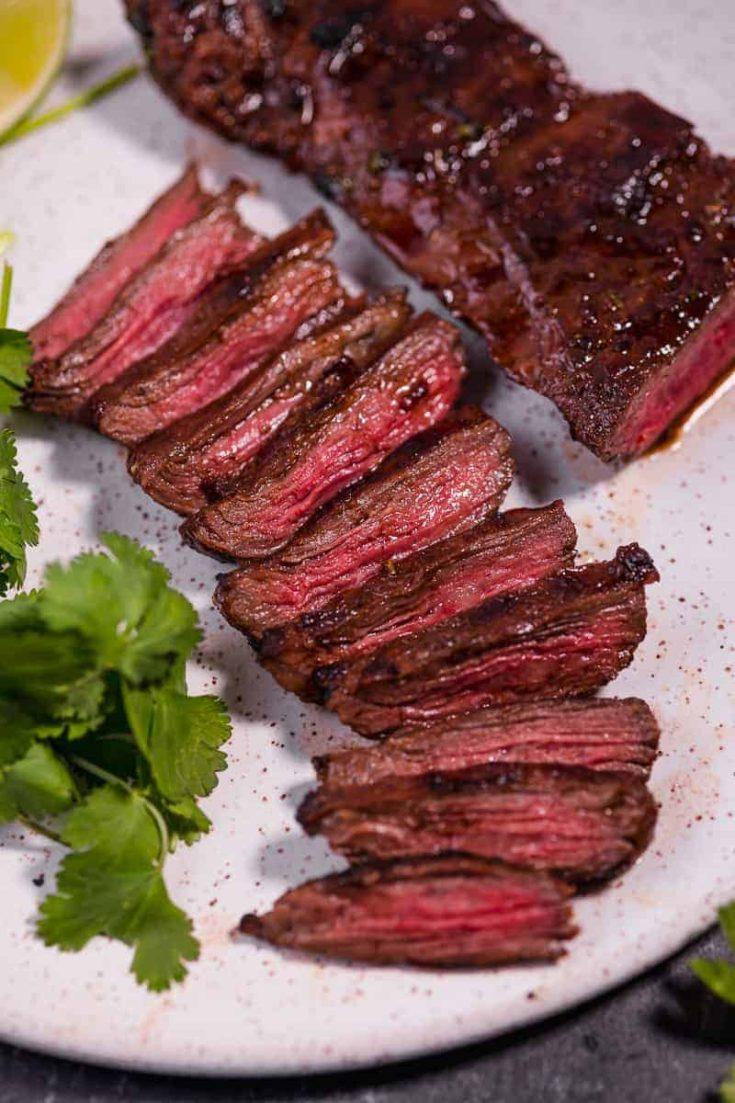 close up of sliced carne asada steak on white plate