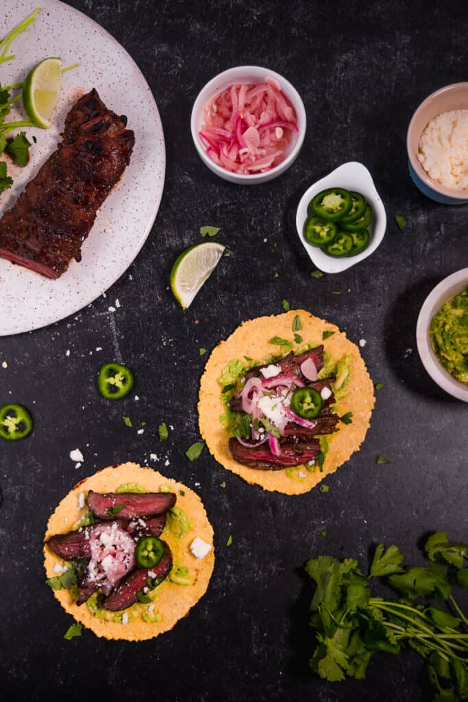 over head photo of corn carne asada tacos surrounded by toppings