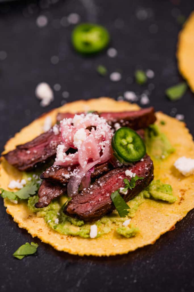 sliced skirt steak on a corn tortilla topped with cotija cheese and pickled red onions