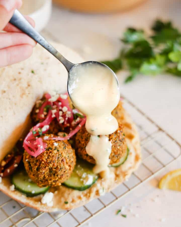 tahini sauce being drizzled over falafel