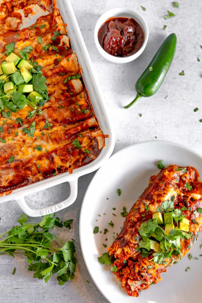 chicken enchiladas on a plate garnished with cilantro and avocados