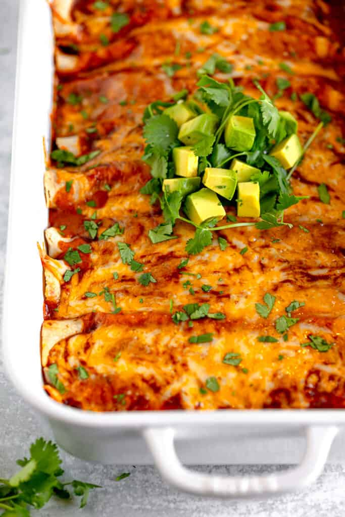 close up of cheesy chicken enchiladas topped with cilantro and diced avocados