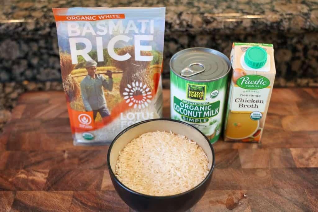 basmati rice bag, coconut milk, and chicken broth on cutting board