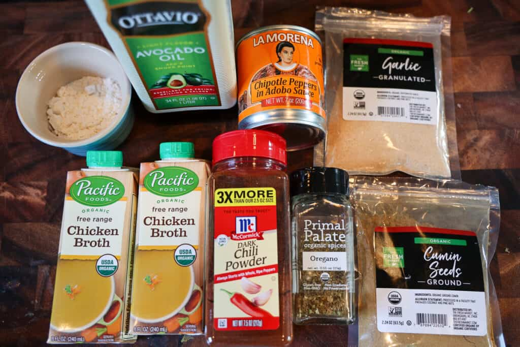 ingredients for enchilada sauce and spices on a cutting board