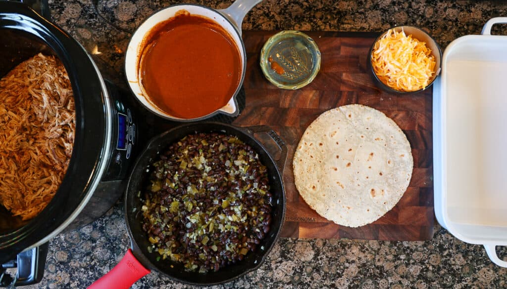 assembly line of tortillas, chicken, cheese, enchilada sauce, and beans