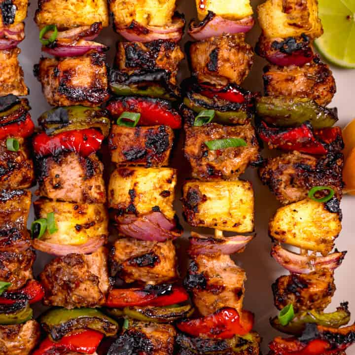 close up of grilled jerk chicken skewers with grilled pineapple