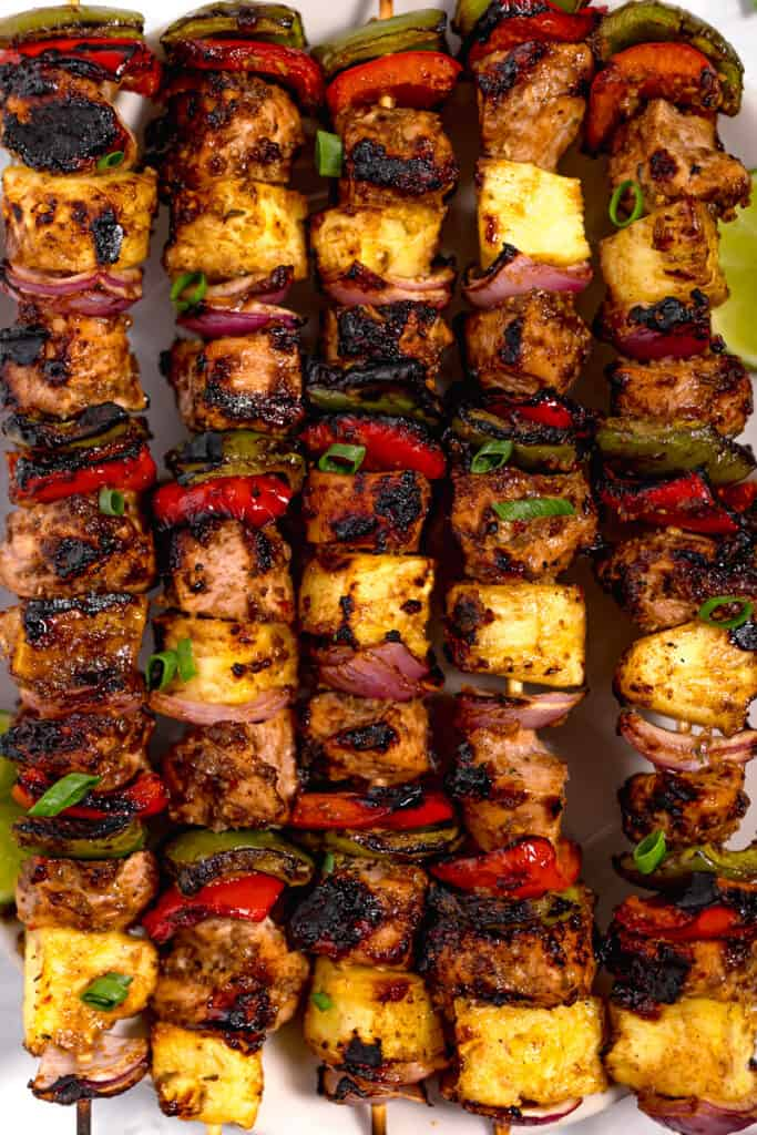 close up grilled jerk chicken skewers with grilled pineapple and bell peppers