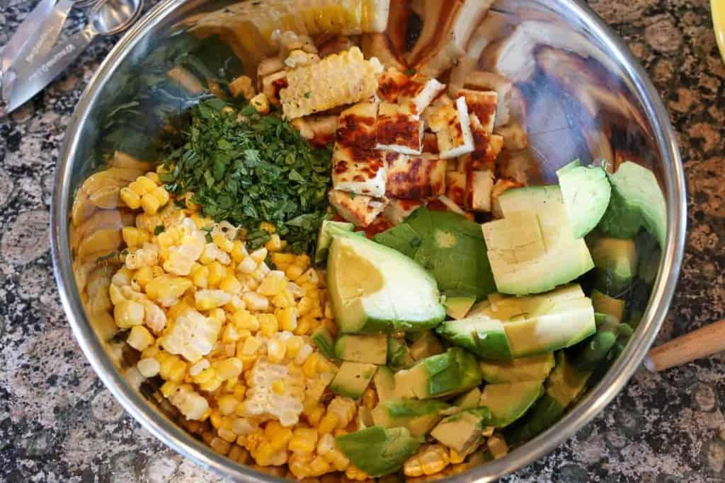 diced avocado, corn, halloumi, and cilantro in a metal bowl