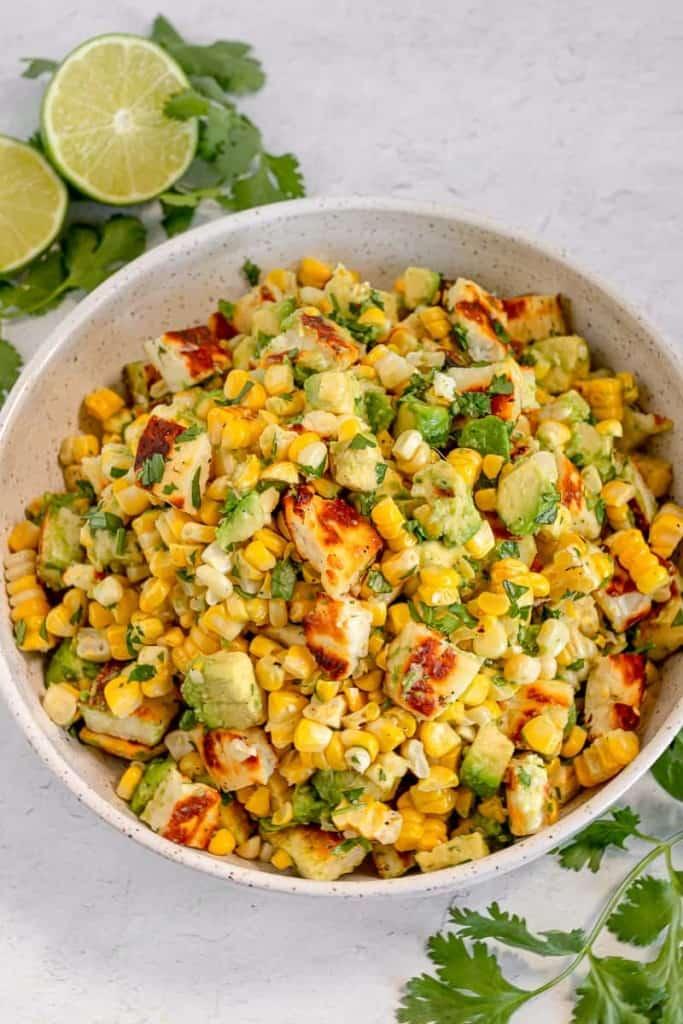 grilled corn, halloumi, avocado, cilantro in a white bowl with limes