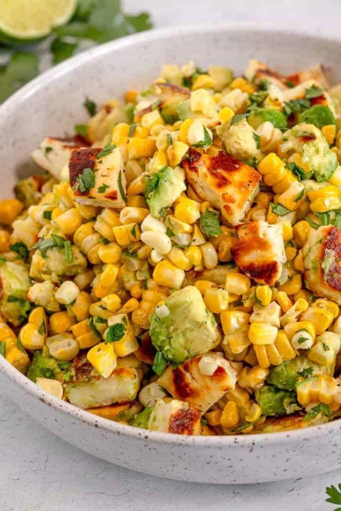 grilled corn, avocado, halloumi cheese, and cilantro in a white bowl