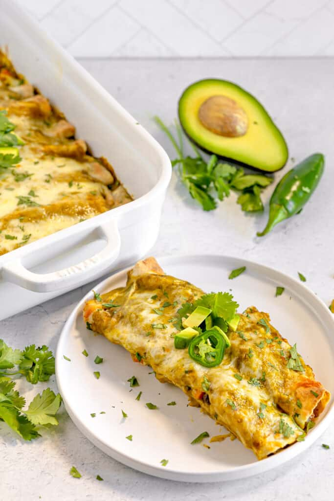 two enchiladas on a white plate with green enchilada sauce, melted cheese, and cilantro avocado