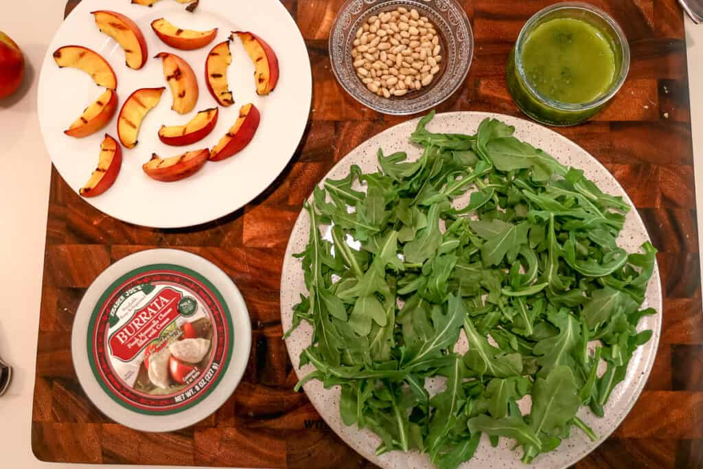 plate of arugula, plate of grilled peaches, burrata in container, ad pine nuts