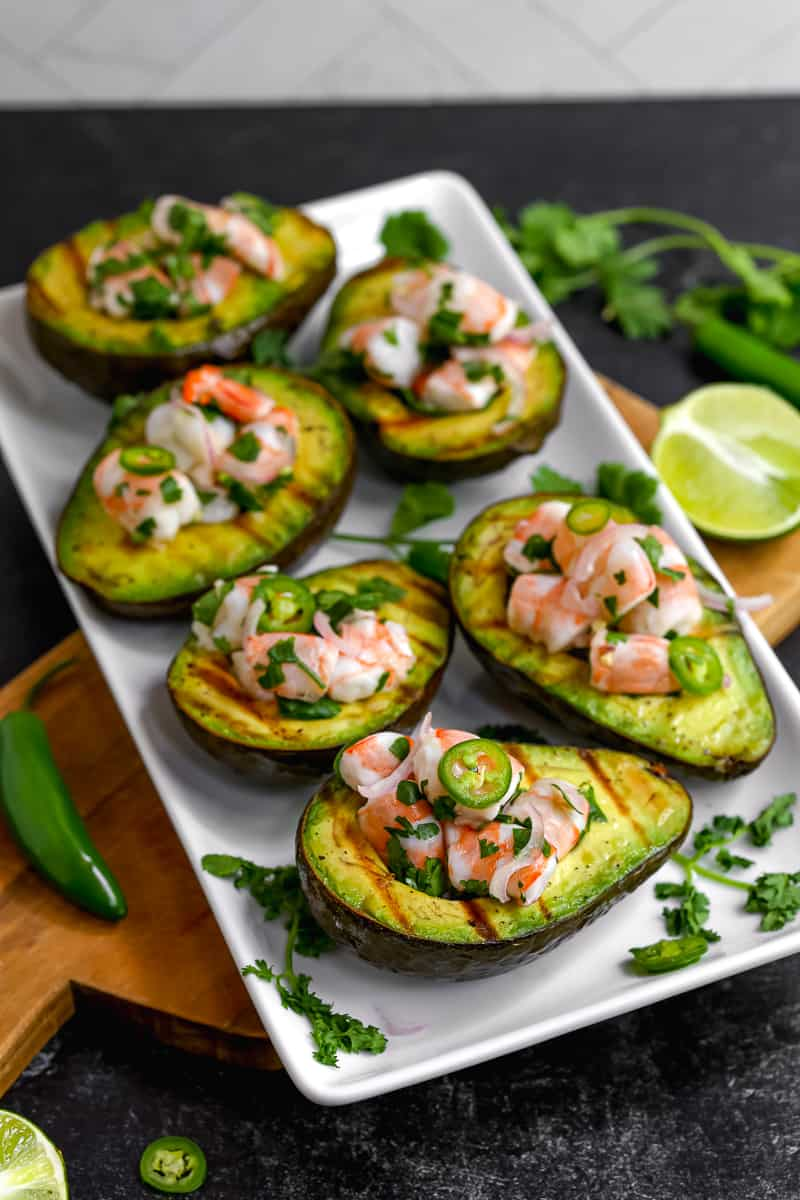 grilled avocado halves with shrimp ceviche and serrano peppers on a white plate