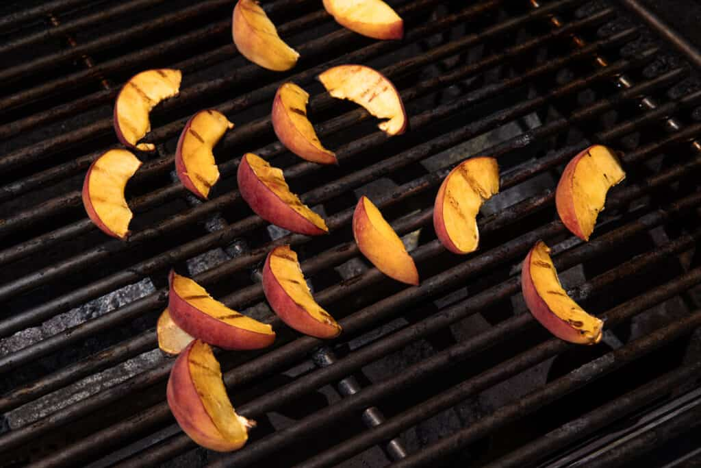 sliced peaches on grill grates