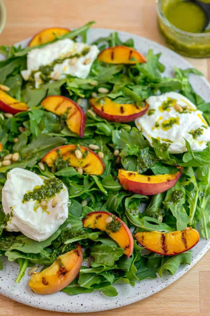 Arugula, grilled peaches, burrata, and basil dressing on a white plate on a cutting board