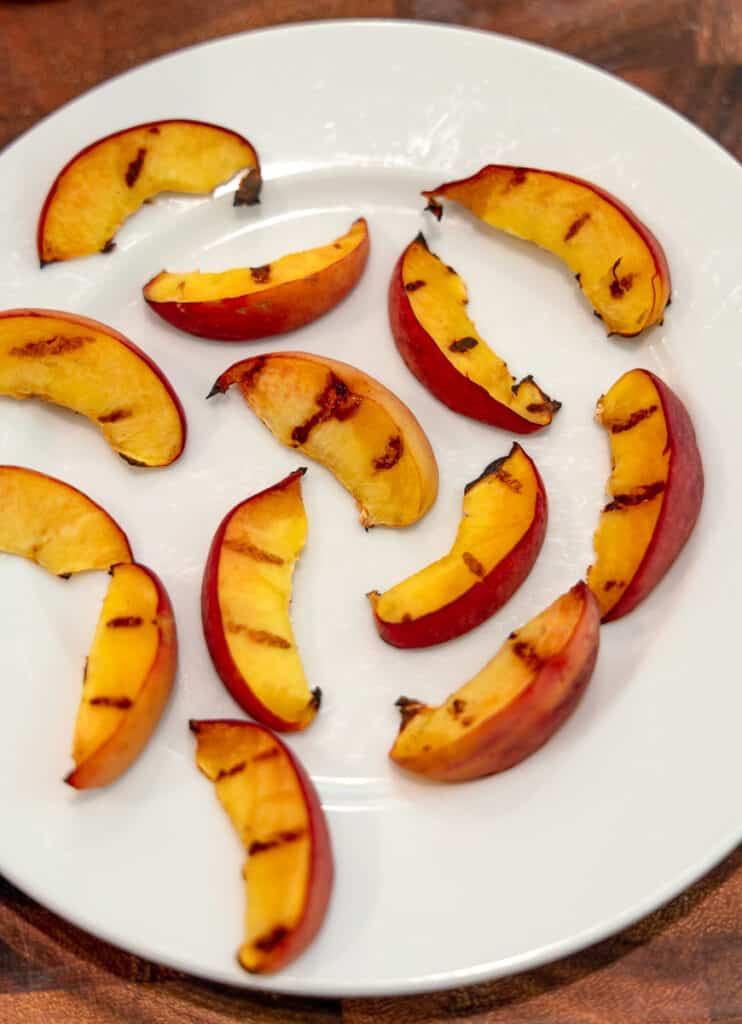 sliced grilled peaches on a white plate