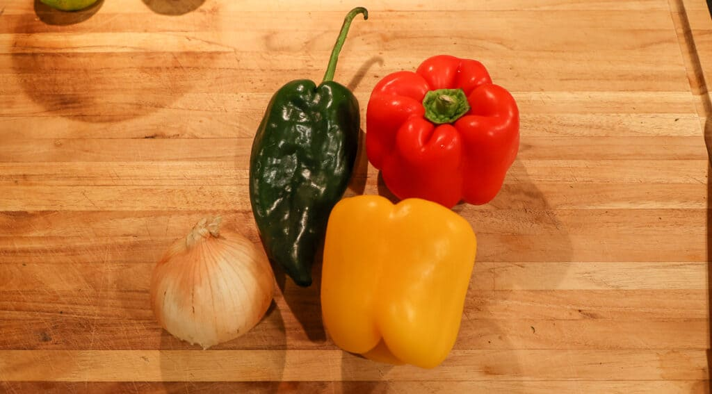 poblano pepper, onion, red and yellow bell pepper on a cutting board