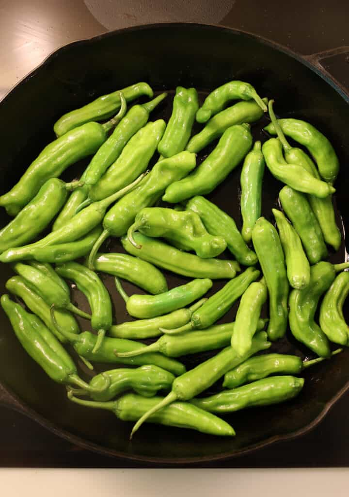 uncooked shishito peppers in a cast iron skillet