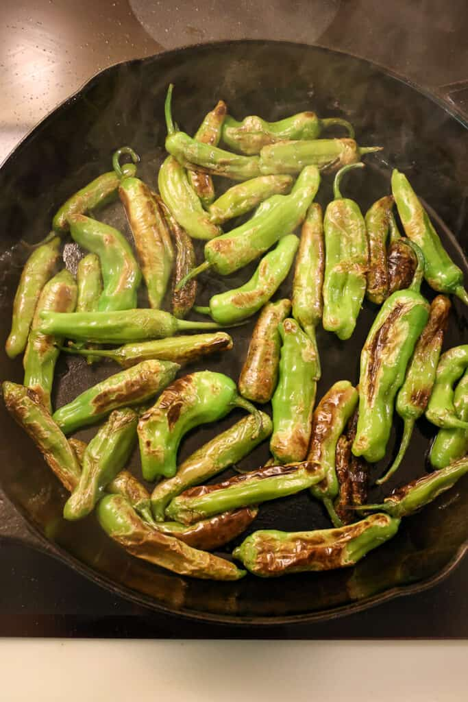 shishito peppers cooking in a cast iron skillet