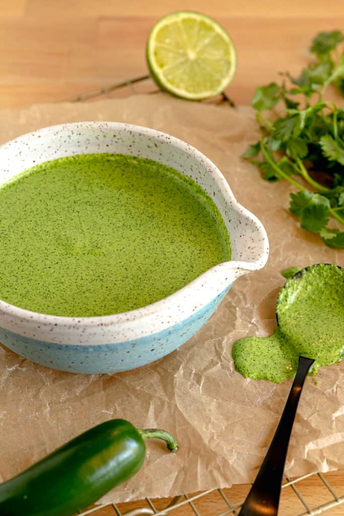 aji verde green sauce in a blue bowl surrounded by cilantro jalapeno and lime