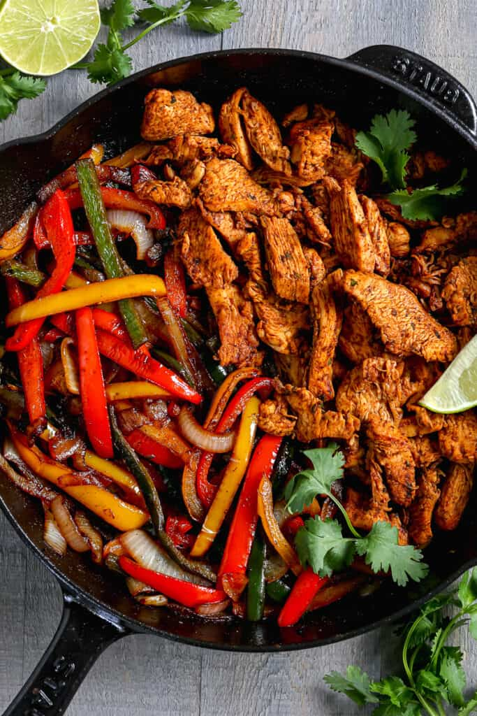 chicken and bell peppers in a cast iron skillet topped with cilantro and lime wedges