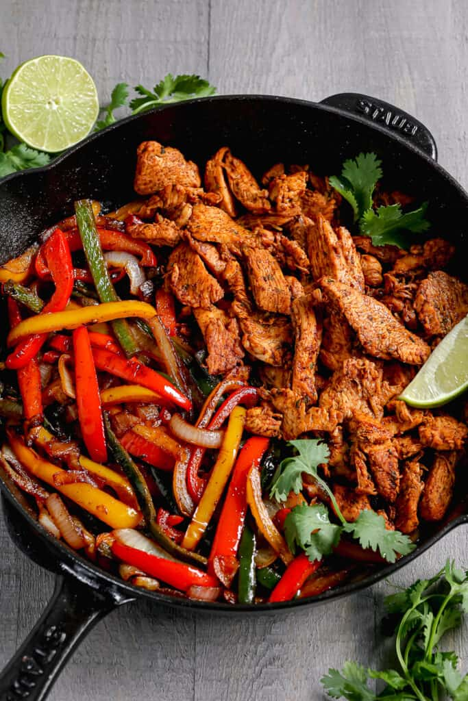 chicken fajitas in a cast iron skillet with lime and cilantro on top