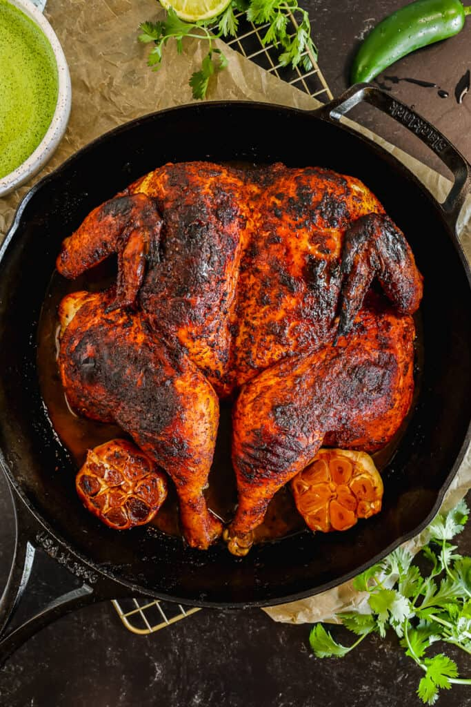 overhead shot of roasted peruvian spatchcocked chicken in a cast iron with roasted garlic