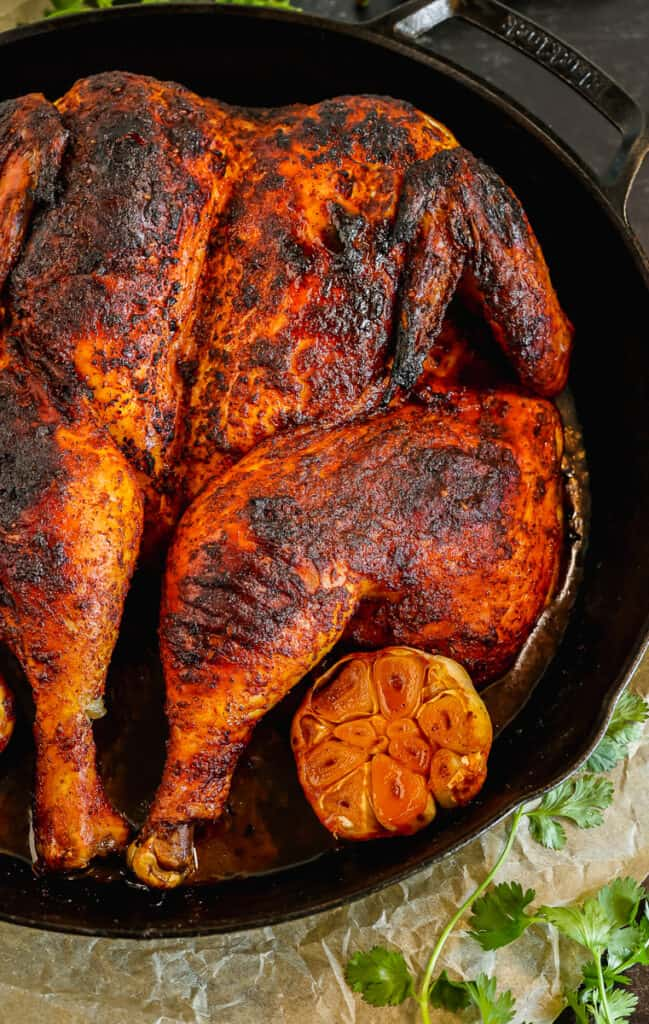 close up of peruvian roasted chicken with crispy skin in a cast iron skillet