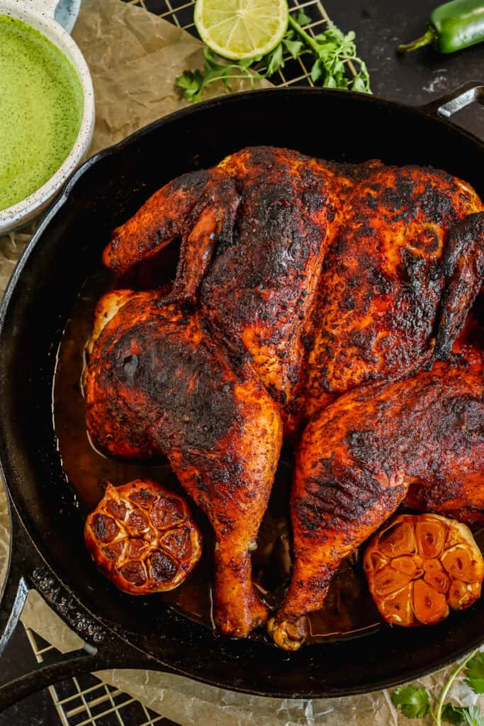 Peruvian roasted spatchcock chicken in a cast iron skillet with aji verde green sauce and cilantro on the side