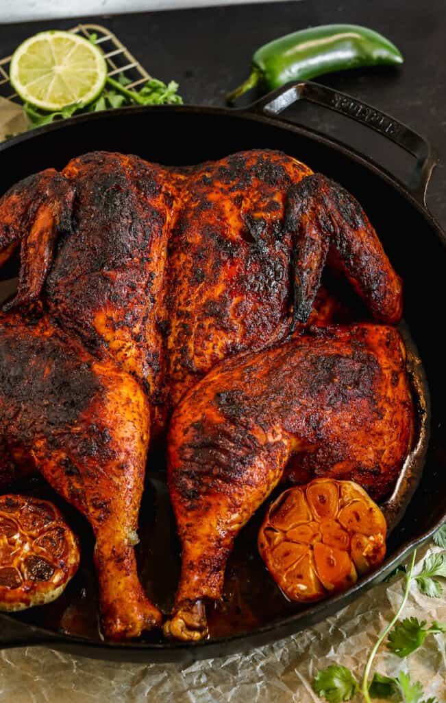 Peruvian roasted chicken in a cast iron skillet with roasted whole garlic