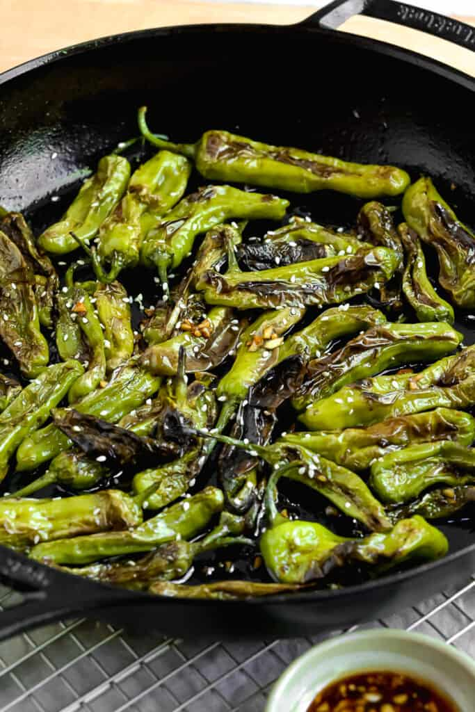 saucy blistered shishito peppers in a cast iron skillet