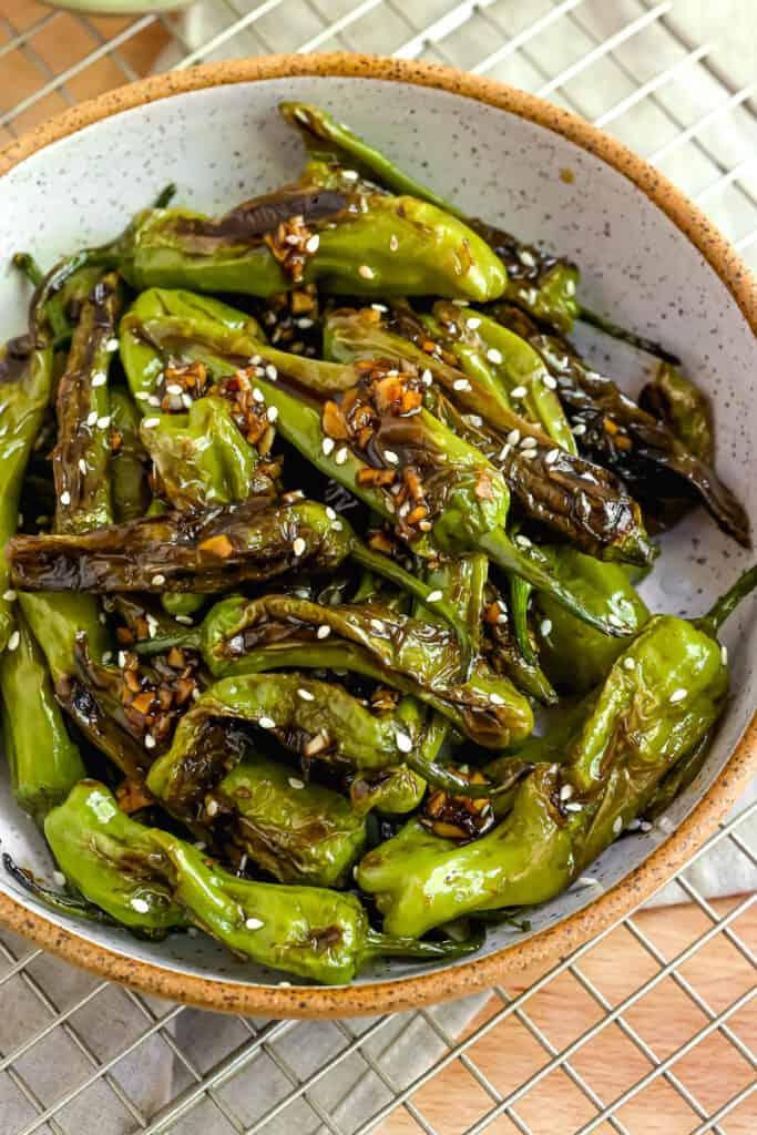 close up of soy garlic blistered shishito peppers in a white bowl