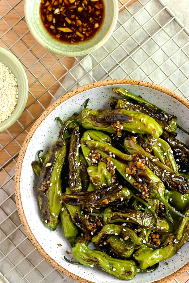 shishito peppers in a white bowl topped with soy garlic sauce and sesame seeds