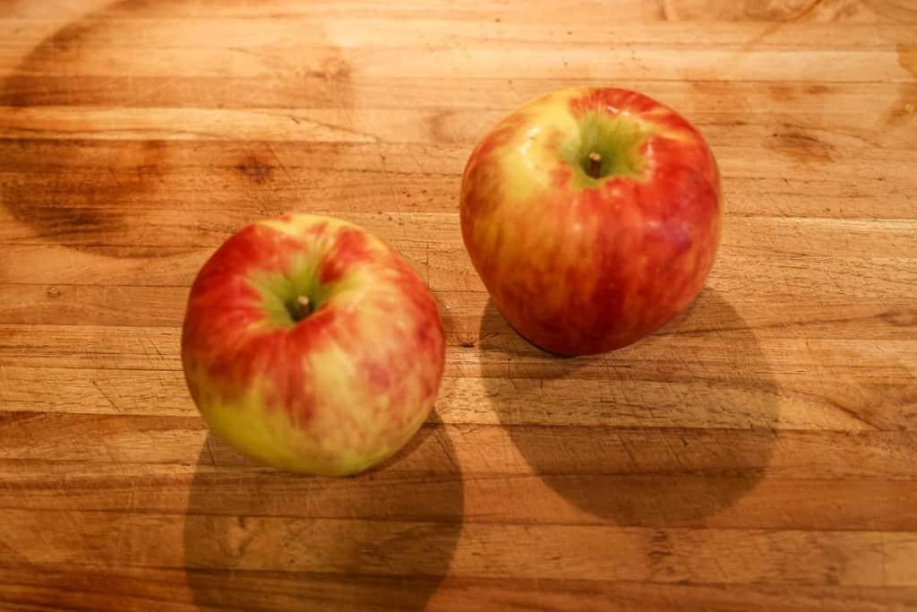 two honey crisp apples on a cutting board