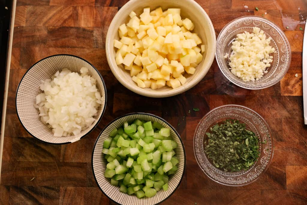 diced apples, diced onion, minced garlic, diced celery, and chopped sage in individual bowls